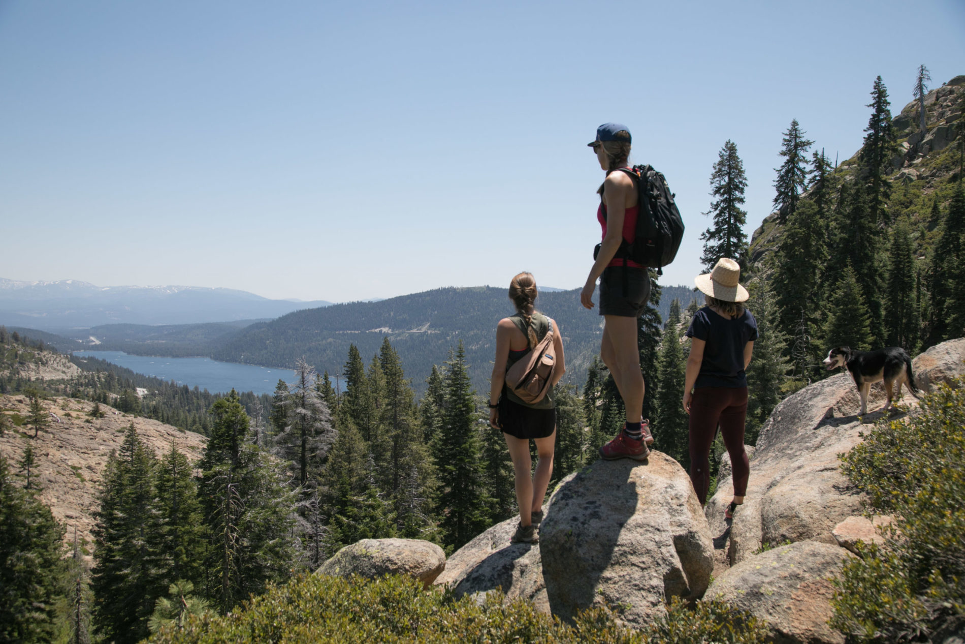 3 women overlooking lake at the top of a mountain