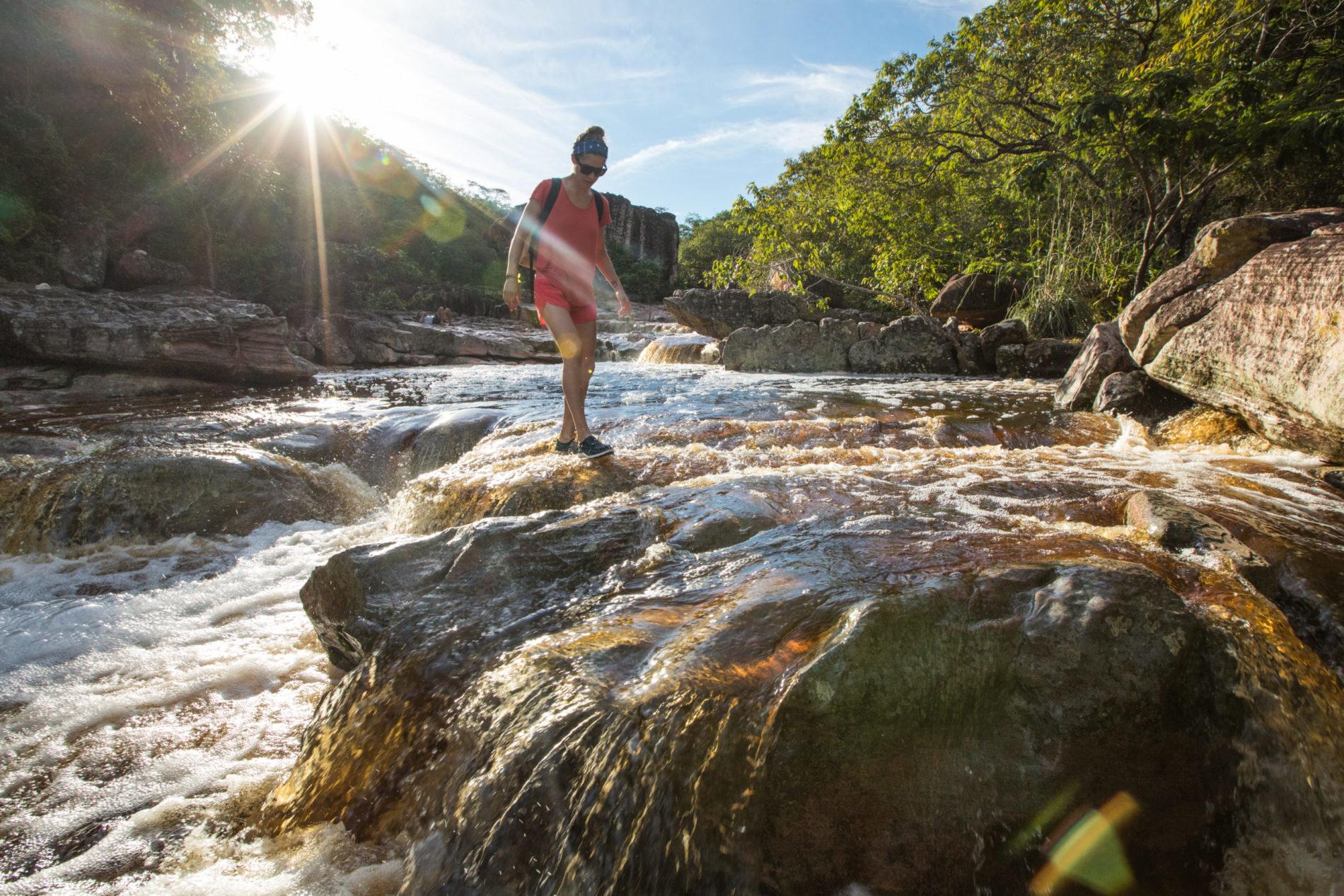 woman walking through a creek